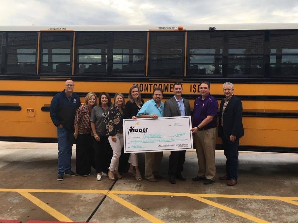 Group of people standing in front of a school bus with a big check.