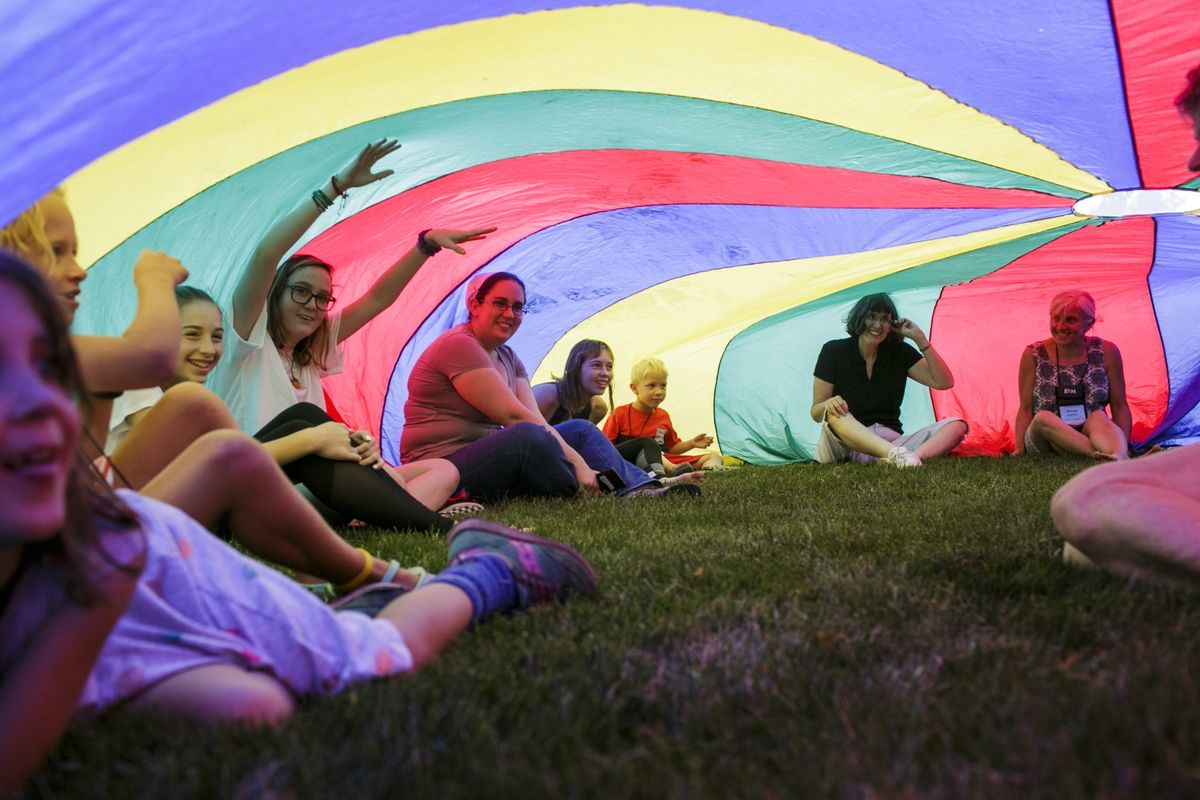 Friends sit under a rainbow parachute