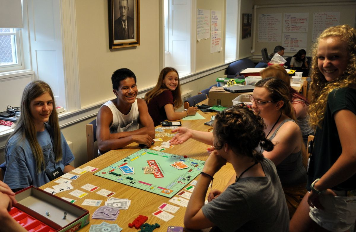 YFs around a table playing Monopoly