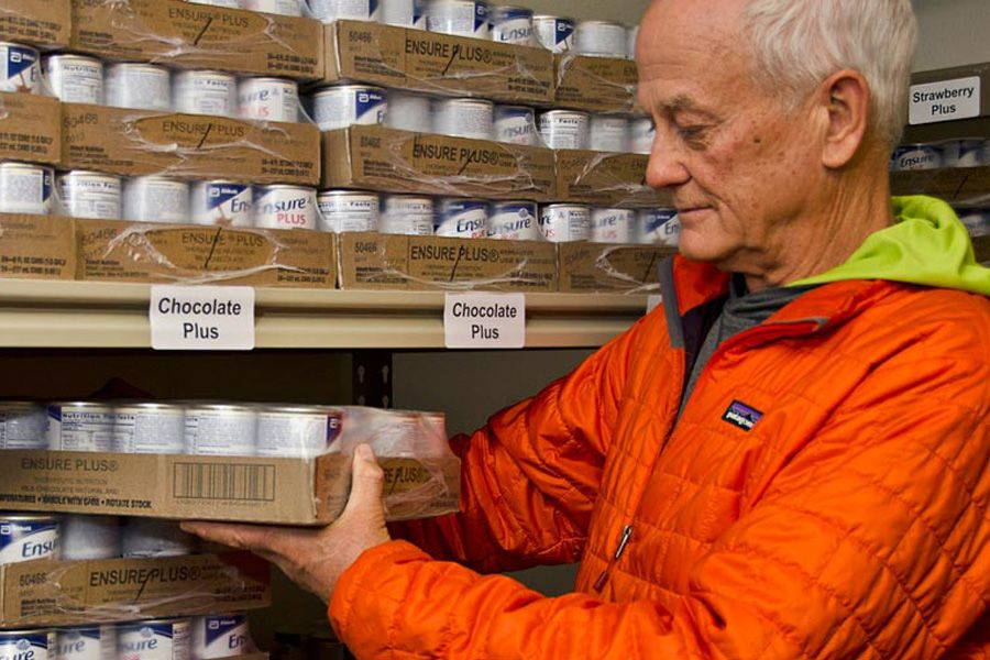 Older male volunteer holding stack of cans in supply room