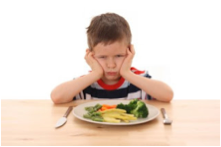 This is a picture of a boy who is unhappy about having to eat his vegetables