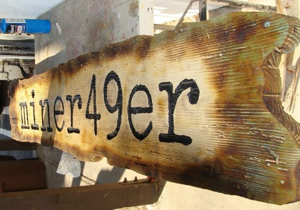 "SA28363 - Close-Up of Antique-Look Rustic Cedar Wood Sign for the ""Miner 49er"" retail Store"