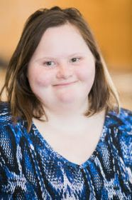 Professional headshot of white woman with Down syndrome smiling at camera