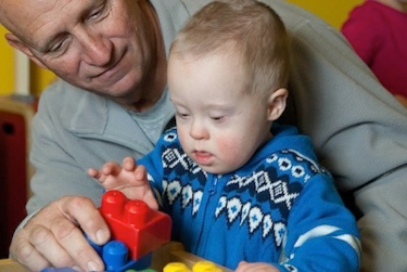 A grandfather playing with his grandson with Down syndrome.