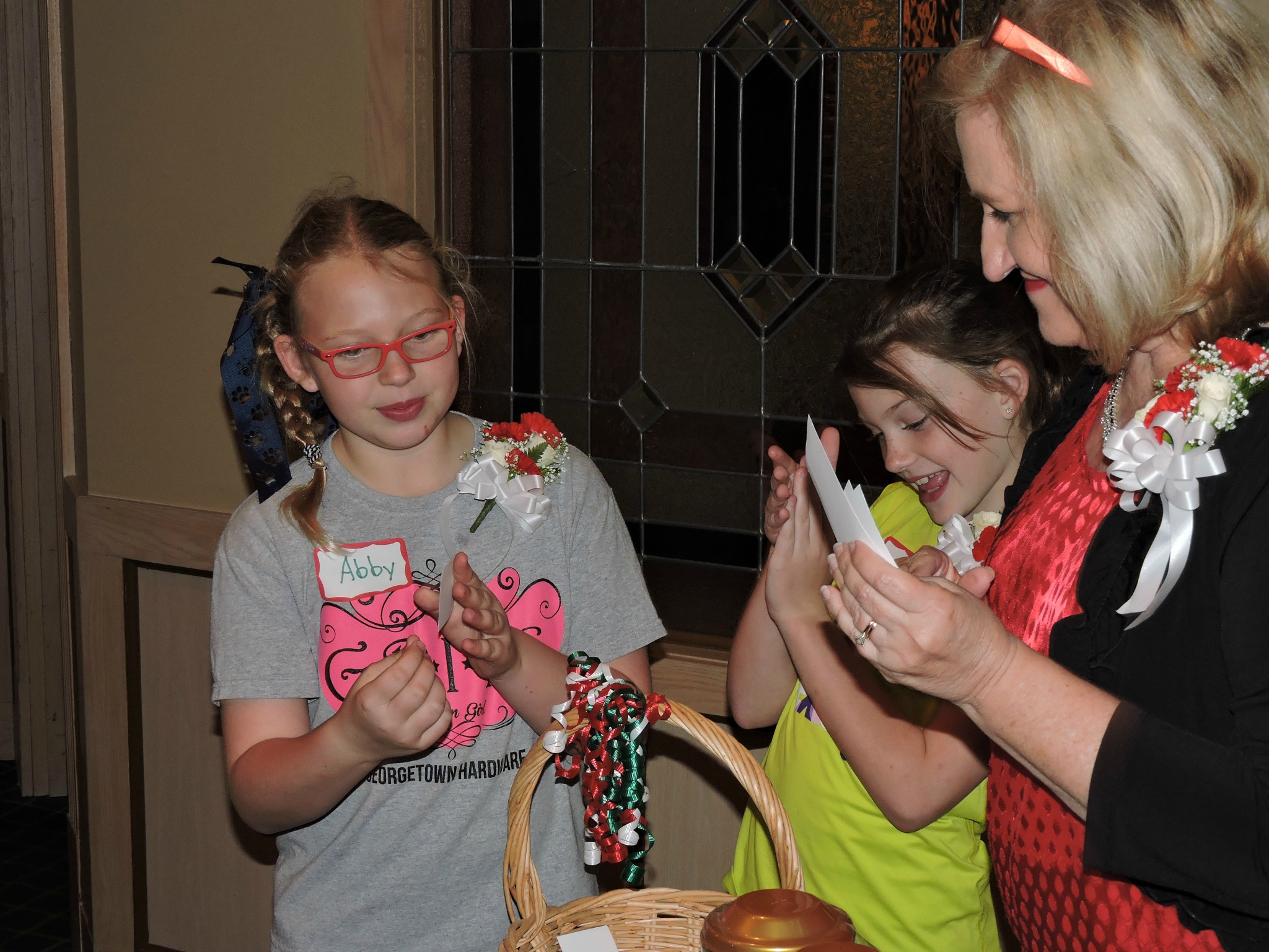Judy Sykes and the Graves girls, Lilly and Abby, give out door prizes