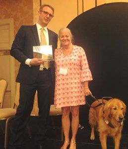 Mark Dunning and Moira Shea, with her guide dog, Finnegan, are shown presenting the award in honor of Dr. Kimberling. (Dr. Kimberling not pictured.)
