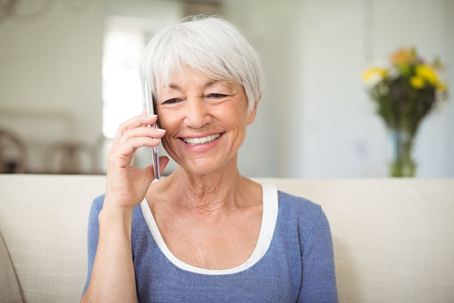 Older woman sitting on her couch, smiling and talking on her cellphone