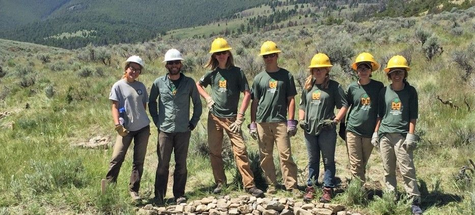 Five youth participants wearing yellow helmets, green MCC shirts and brown pants are standing with two adult leaders wearing white helmets.  They are standing on rocky berm with sage brush plains and rolling hills behind them.