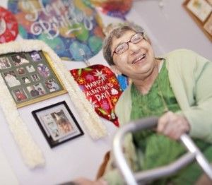 Elderly woman PSRS supports wtih her walker, smiling in front of a wall in her bedroom covered with photos and decorations
