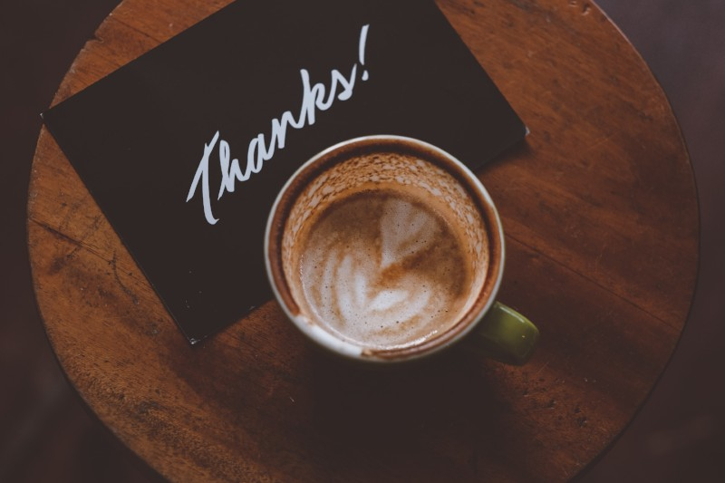 Thank you card next to a cup of coffee