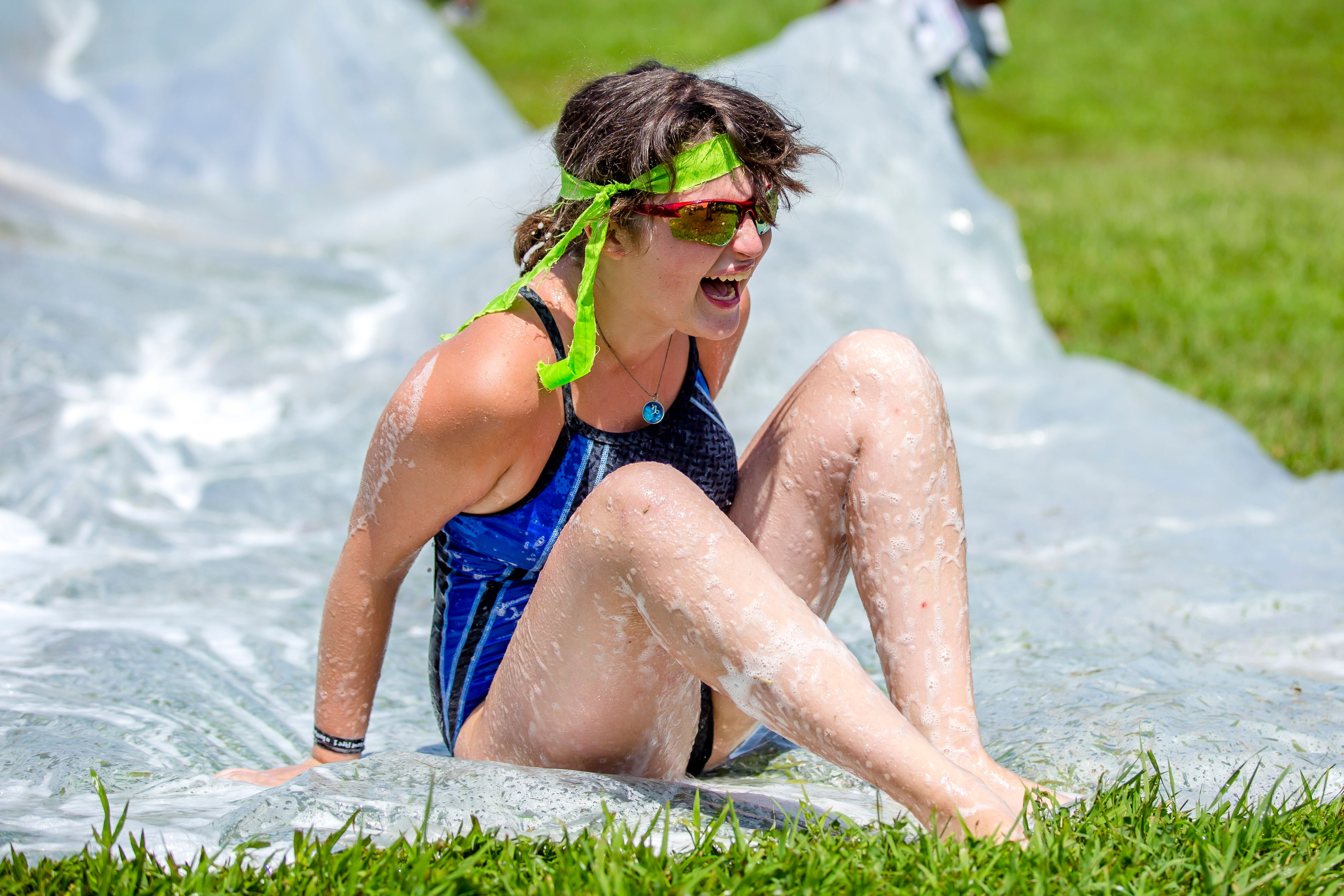 A camper laughs after enjoying a ride down the slip-n'-slide