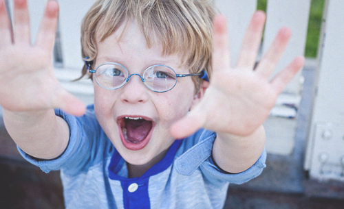 Photo of little boy with blue glasses and a blue shirt