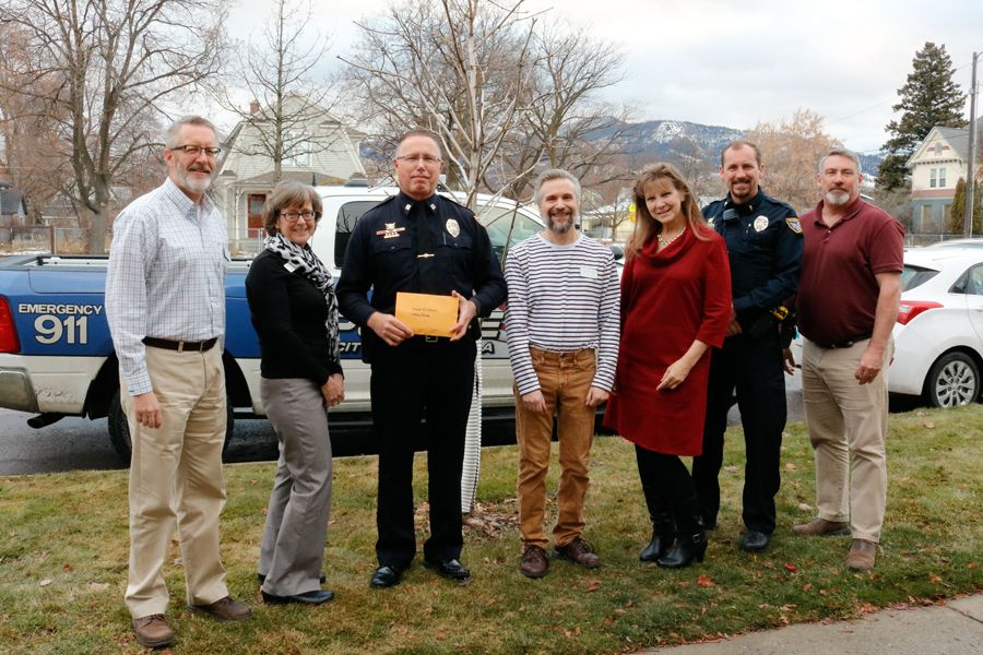 Missoula Police Department representatives standing outside in front of police cars presenting money raised to Missoula Services Staff, everyone is smiling