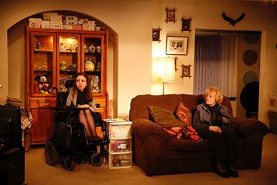 (L to R) Shannon DeVido is sitting in her power and Lynne Lipton is laying down on the couch and wearing dark clothing. They are both watching the TV.