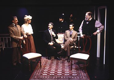 George Ashiotis, Melanie Boland, Nicholas Viselli, Richard Simon, Gary Bergman, Michael Dee, and Jerry Lee Photos by Carol Rosegg. A group of people who are dress formally in a dimly lit room. They are talking and trying to solve the mystery.