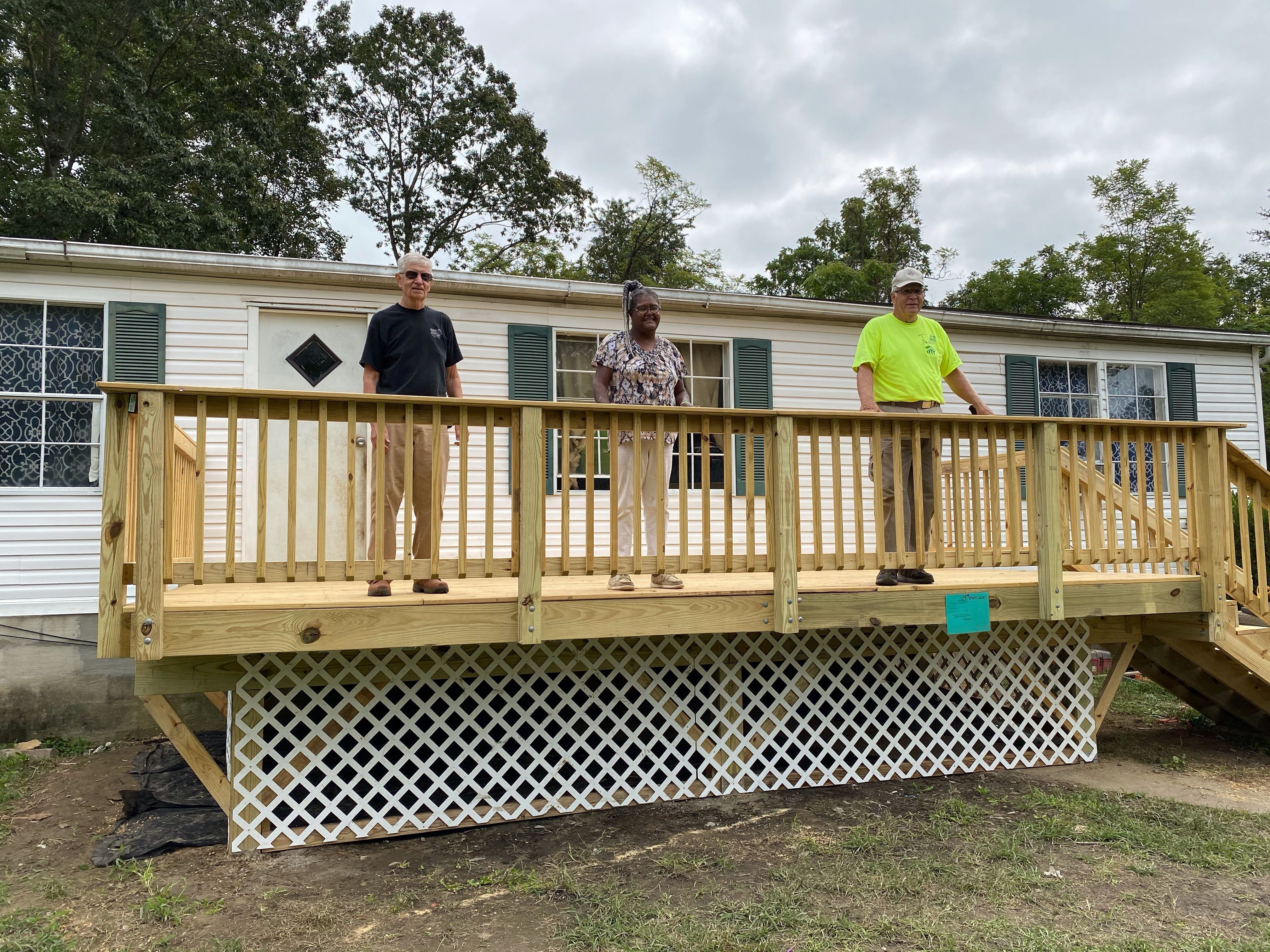 Three people standing on a newly repaired deck.
