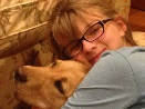 Bella (the blogger's daughter) smiling at the camera while hugging a dog