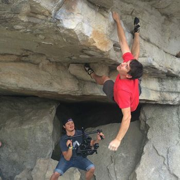 Alex Honnold holds on to a roof with one hand. A camera person films from below