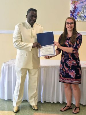 Instructor hands certificate to TBH Staff Member