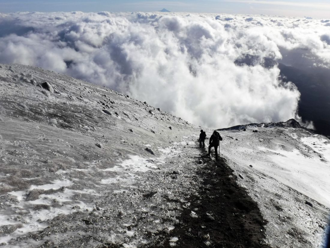 An icy view from the Summit Rim above the clouds, two climbers hiking down