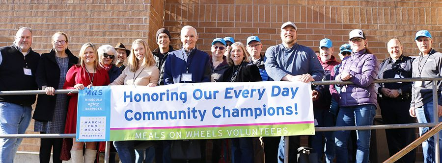 "Male and female community members stand outside smiling holding a sign that reads ""Honoring Our Every Day Community Champions!"""