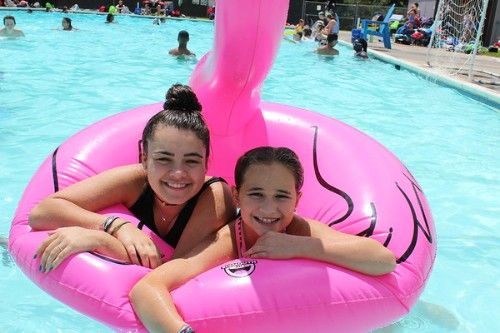 Campers smile on a float in the pool.