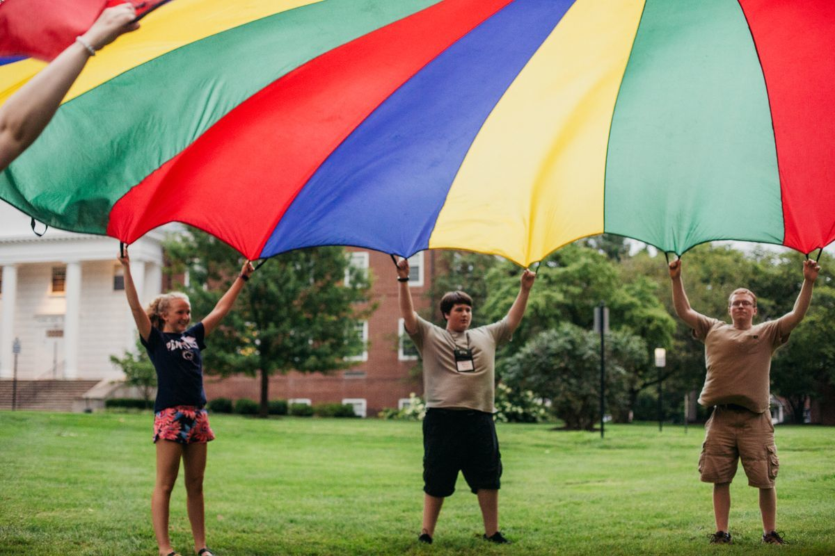 3 people in view, lifting a rainbow parachute over their heads