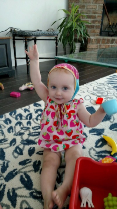 Photo of Emma playing with toys while her hand is raised