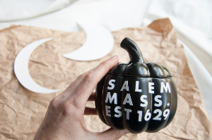 Black pumpkin with text: SALEM MASS. EST 16921, brown paper, paper crescent moon cut outs for DIY project.