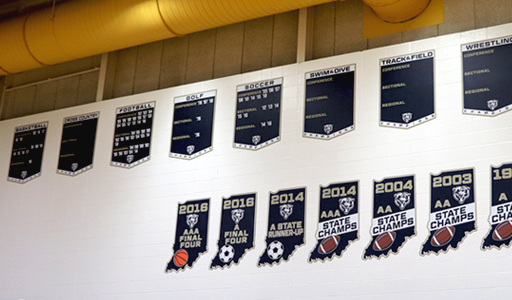 Gym wall with team championship boards and state champ signs, custom signs