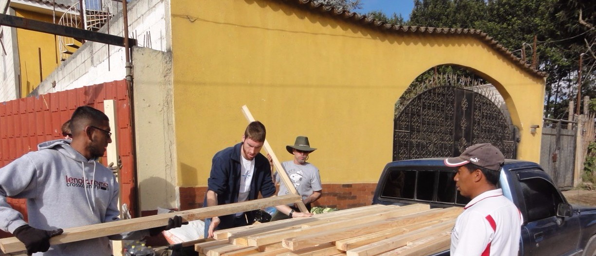 Volunteers loading wood to build beds