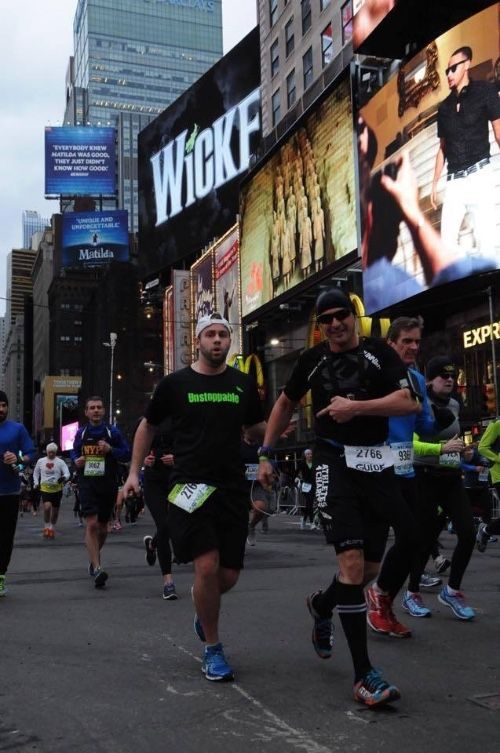 Photo of Brian running with his sighted guide, Marco on a tether in Times Square