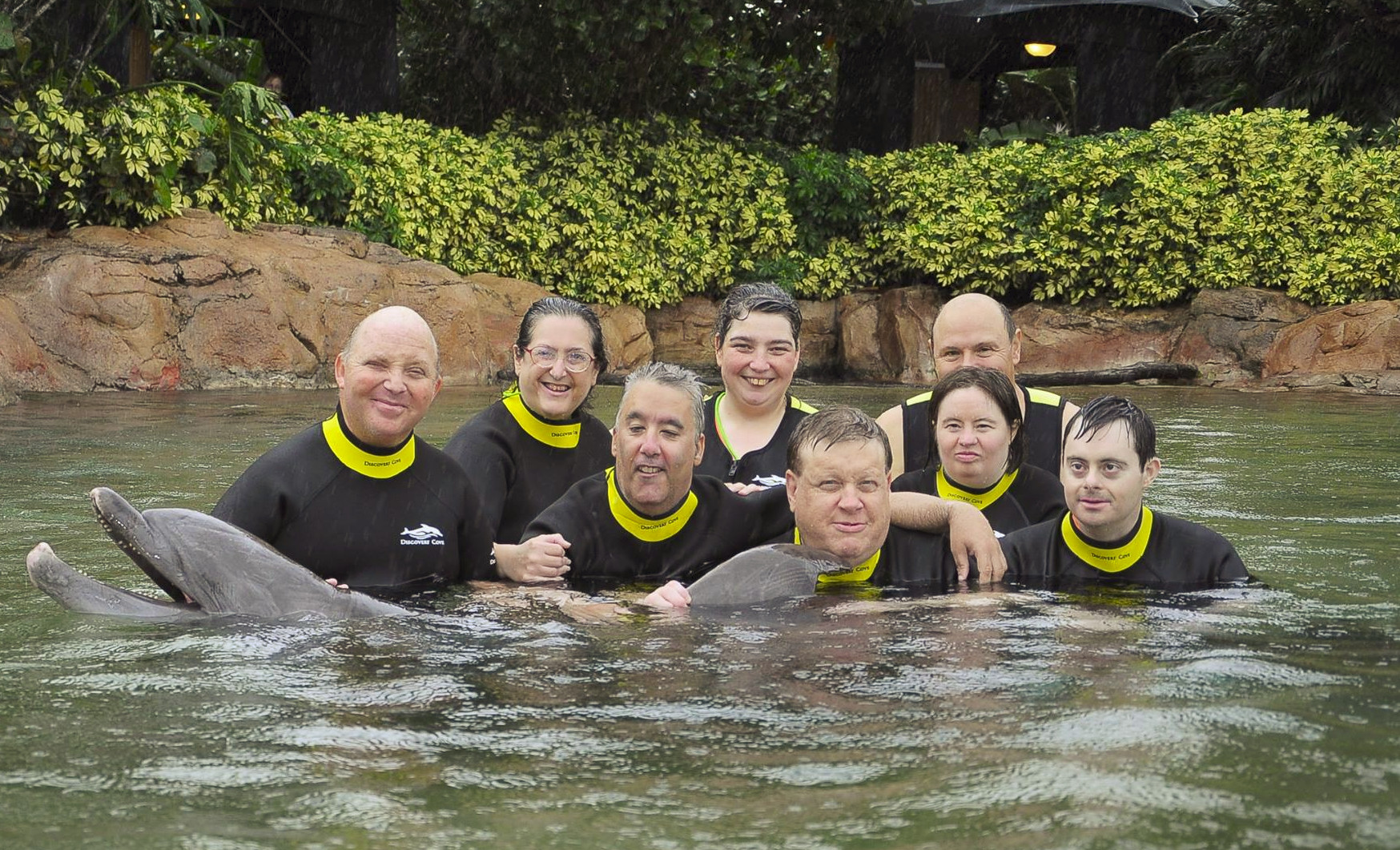 Recreation group poses while swimming with a dolphin