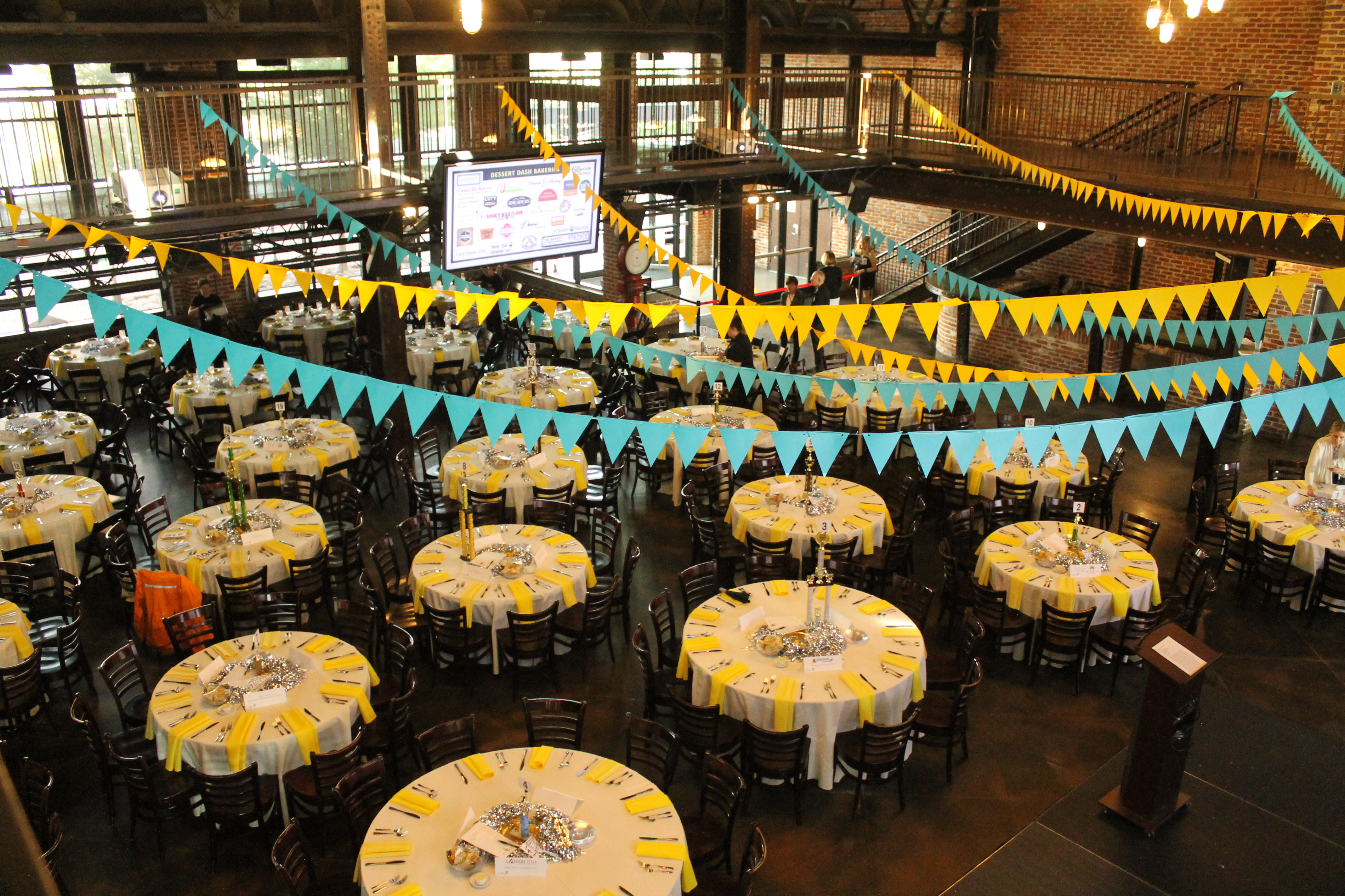 Large room full of circle tables with silver pom poms laying on each table