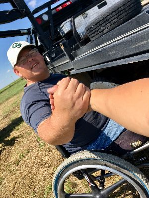 Brady Haynes shaking hands from a wheelchair on his farm.