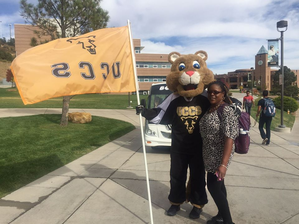 Student standing with UCCS mascot on campus