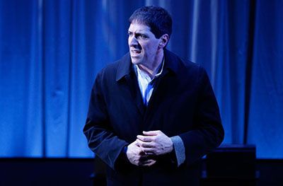 Nicholas Viselli is wearing a black coat and he is trying to keep his hands warm. He is turning his head to left and there is a spotlight on him. There are blue curtains in the background flapping to the side.