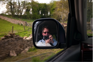 Phot of a man taking a photo of himself in a car mirror