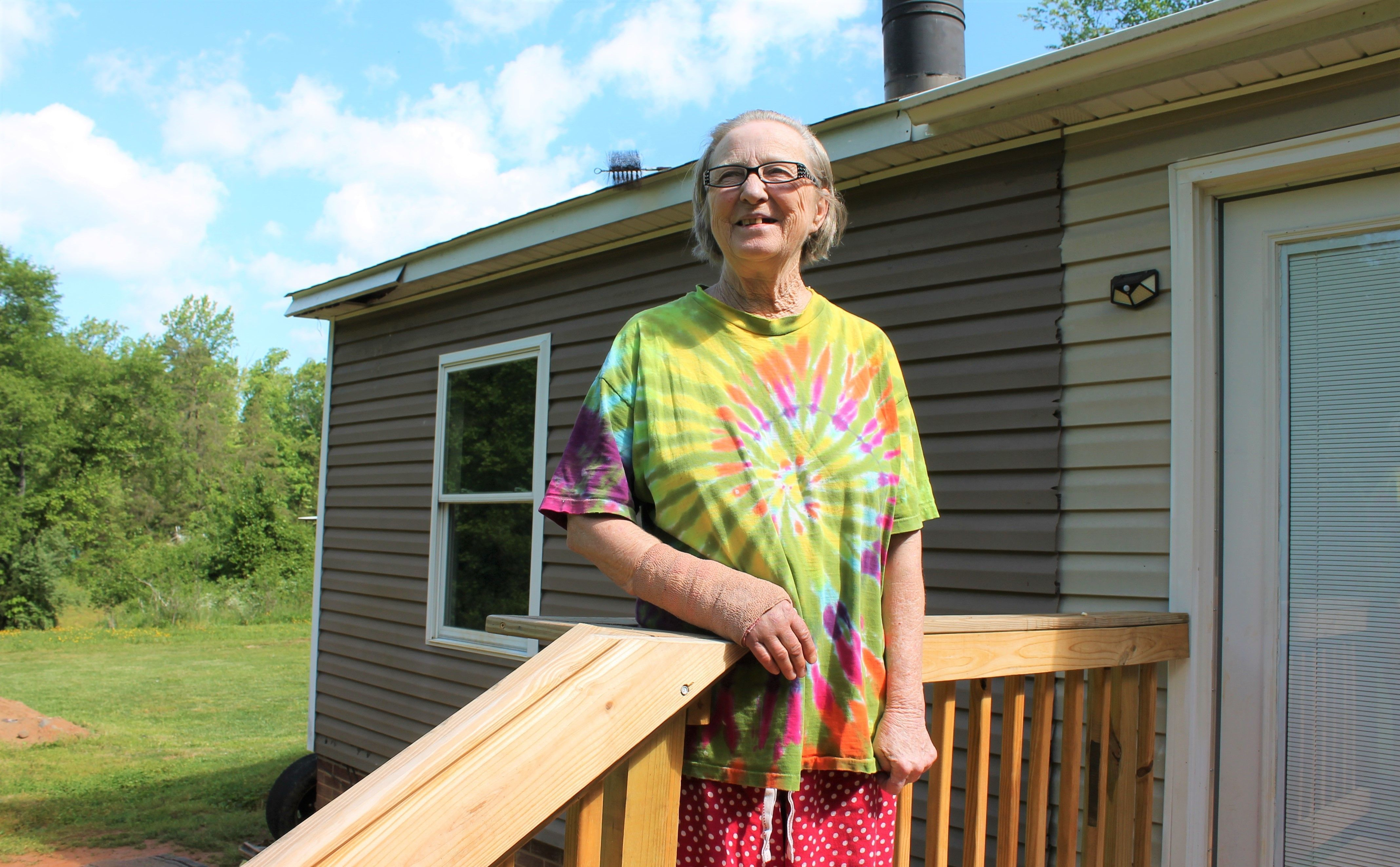 Elderly woman standing on a porch.