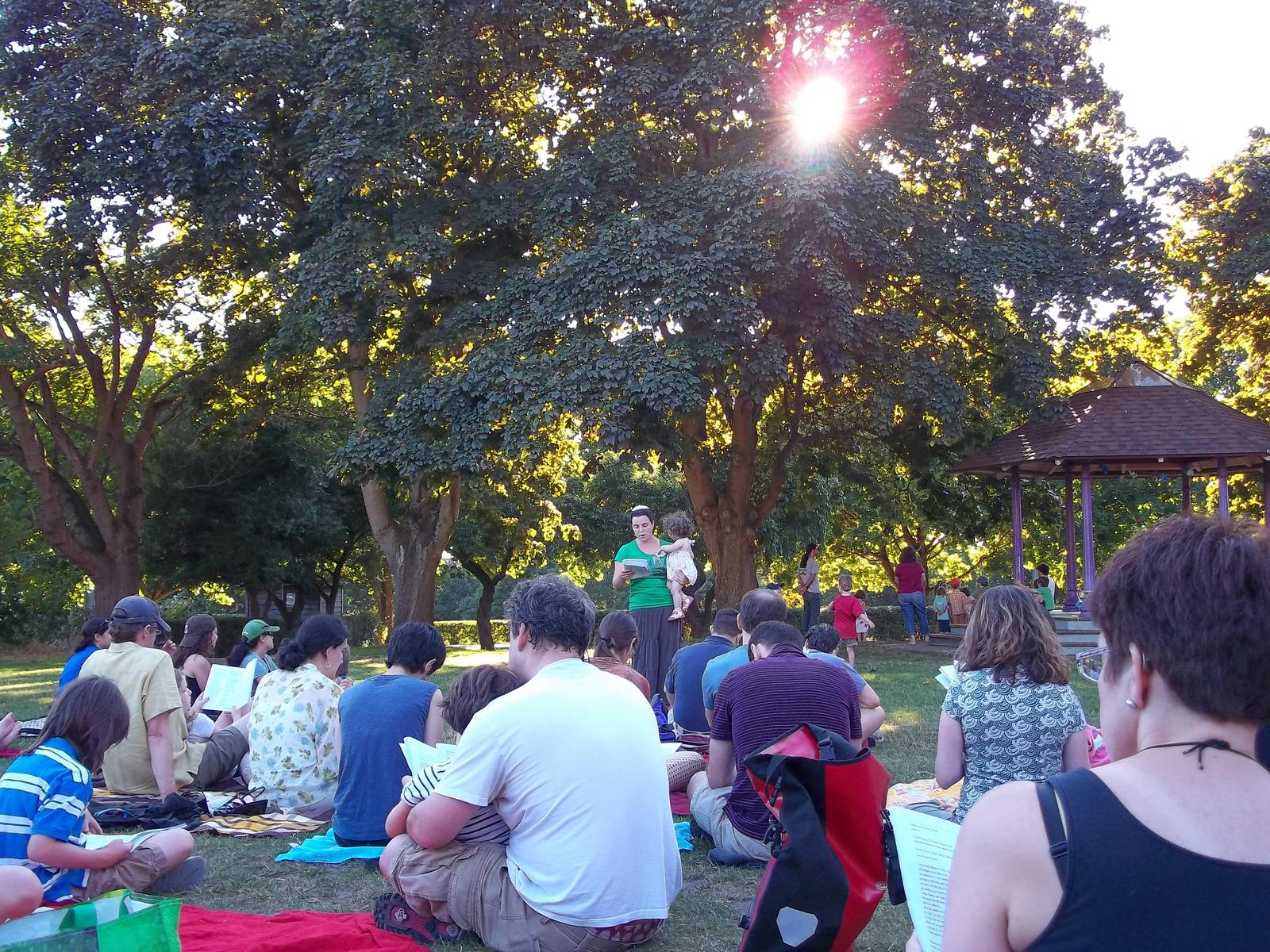 Rabbi Nussbaum leading a Shabbat service in the park.
