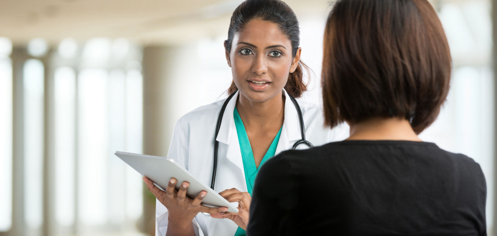 Doctor holding a chart and speaking with a patient