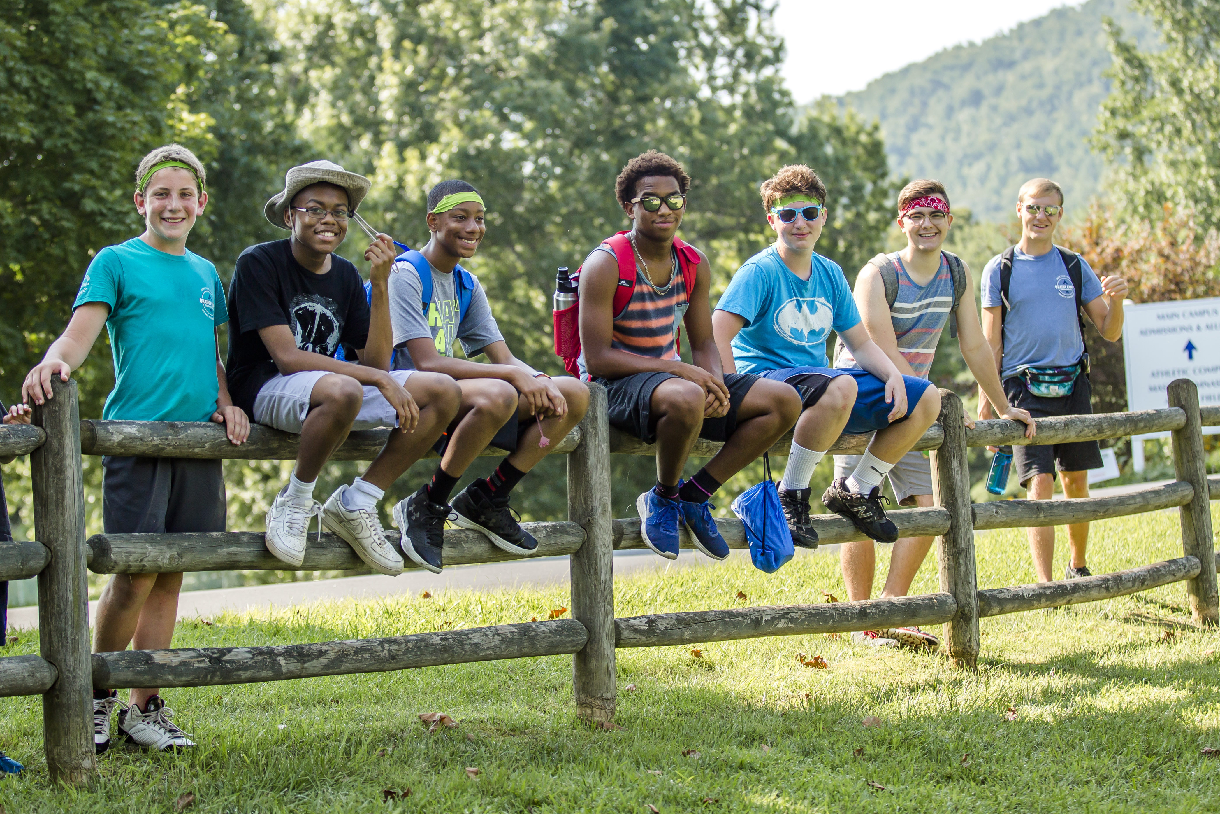 Campers sit on a fence, smiling, and pose for a photo.
