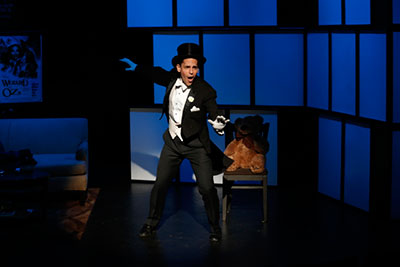 Stephen Drabicki is wearing a tuxedo with white gloves and a black top hat. He is a magician and he is performing a magic trick in a dim lighting.