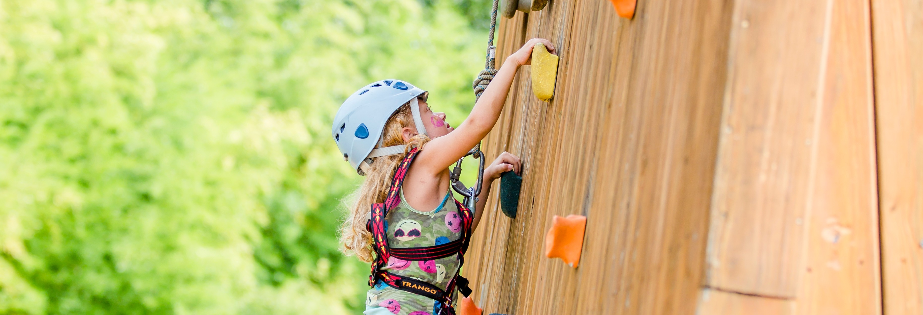 A young camper climbs the rock wall.