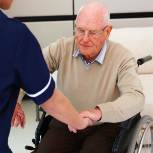 Older man in wheelchair being helped out of chair by personal care attendant