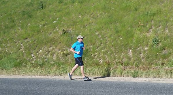Photo of Ryan running on the road in front of a grassy hill