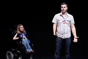 (L-R): Shannon (Mary) is sitting in a power wheelchair and wearing a blue shirt with jeans. She's listening to David (Toby) who is standing, wearing a plaid shirt with jeans. He also has a name tag on his shirt. He has his arms out to the side.