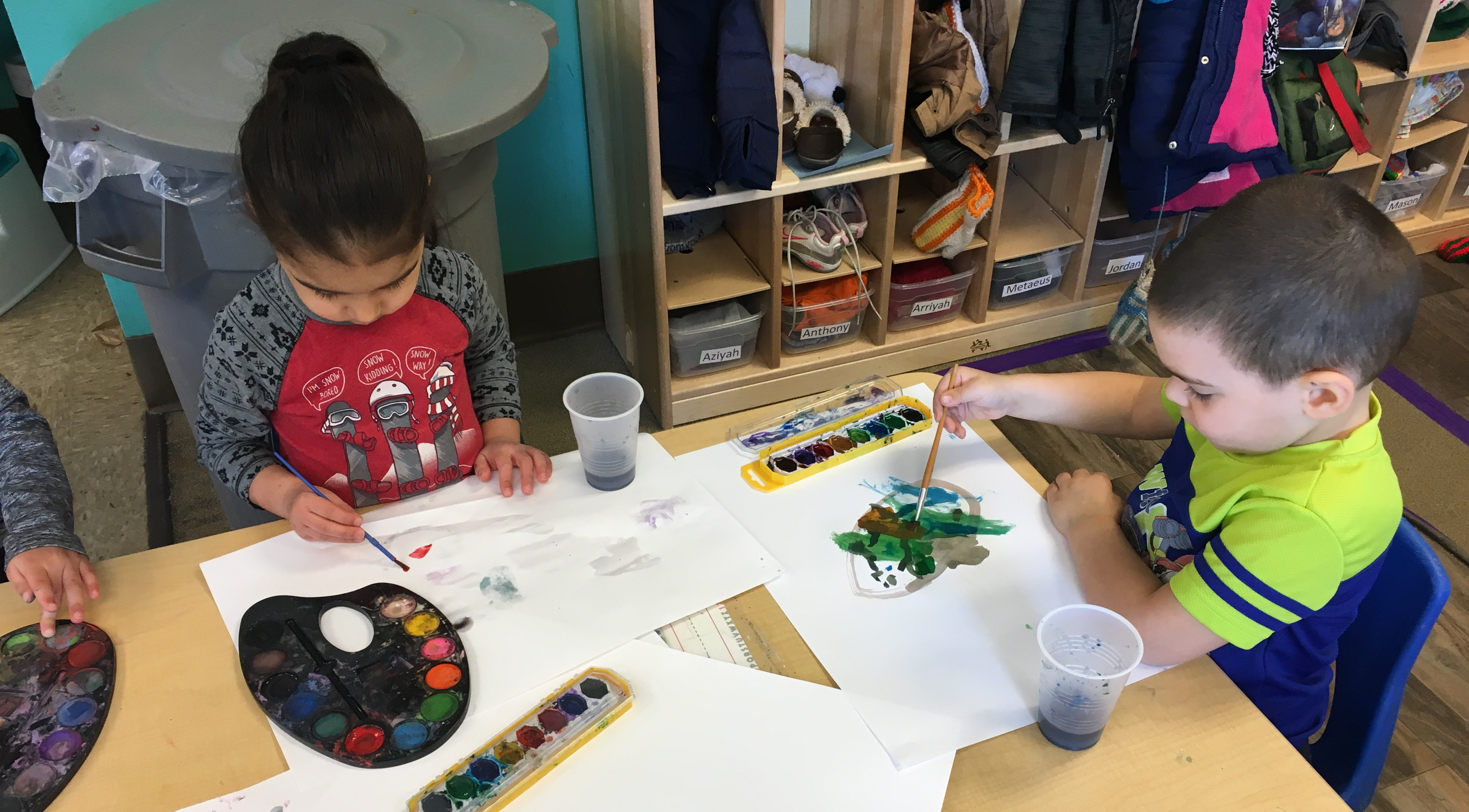 Two children use watercolor paints to make pictures.
