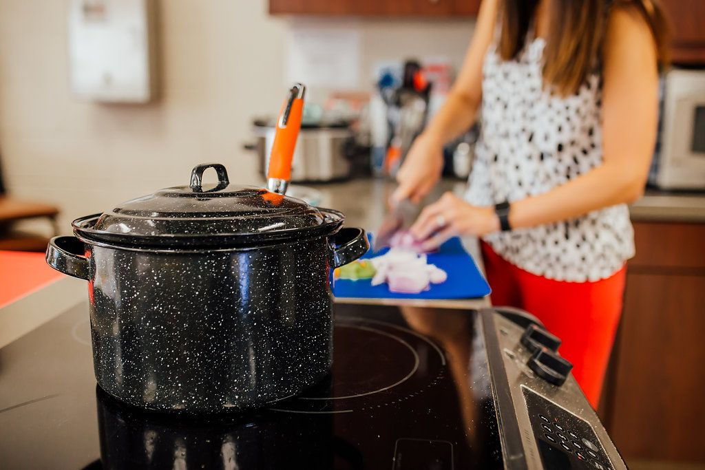 A pot on a stove with a woman cutting vegetables in the background.