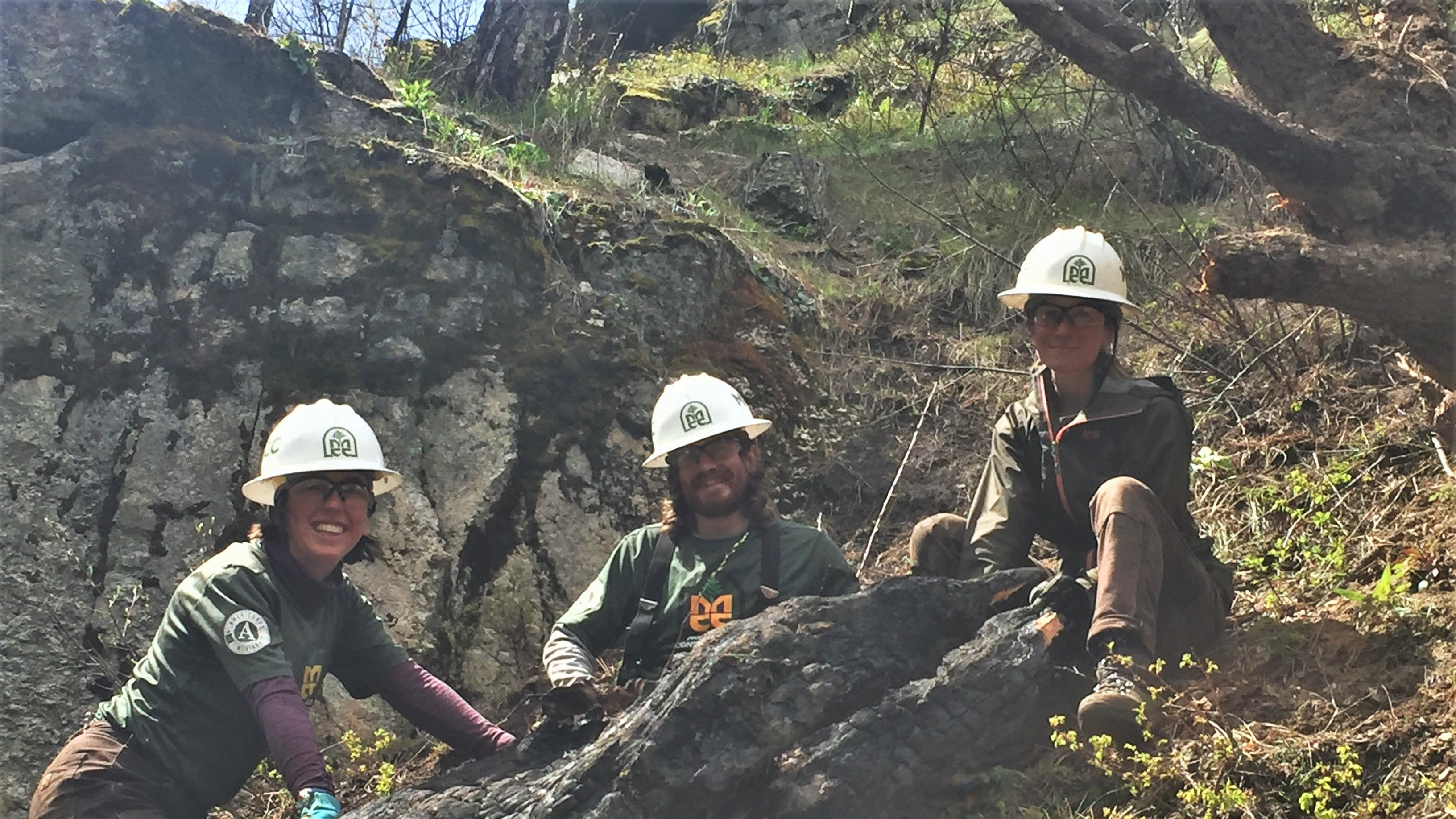 Three crew members with white MCC helmets smiling and standing on a hill loving getting outside